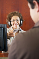 Hispanic businesswoman in headset handing credit card to customer