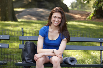 Caucasian woman sitting on park bench