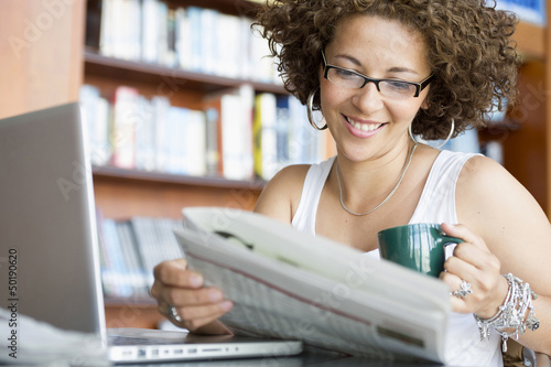 Hispanic woman reading newspaper in library