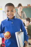 African American boy holding apple in classroom