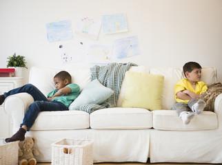 Angry boys sitting on sofa