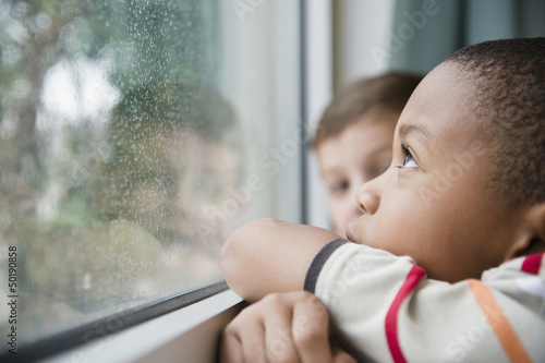 Boys looking out window together