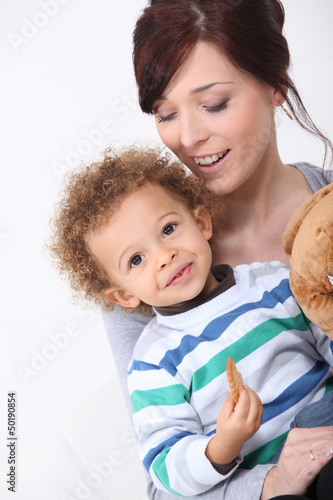 Mother and her son eating a cookie.