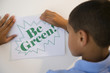 Hispanic boy putting up be green sign