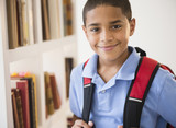 Smiling Hispanic boy carrying backpack