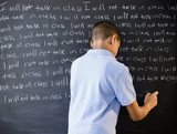 Hispanic boy writing punishment on blackboard