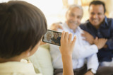Hispanic boy taking photograph of father and grandfather