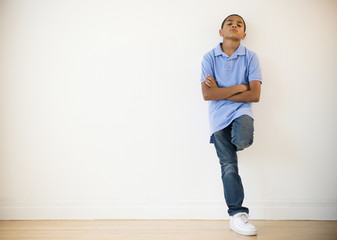 Frustrated Hispanic boy leaning against wall