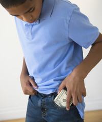 Hispanic boy putting in pocket