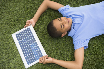 Hispanic boy holding solar panel