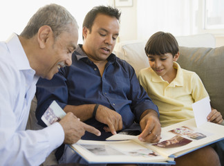 Hispanic grandfather, father and son looking at photo album