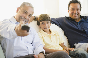 Hispanic grandfather, father and son watching television