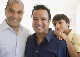 Smiling Hispanic grandfather, father and son