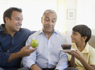 Hispanic father and son offering grandfather apple and cupcake