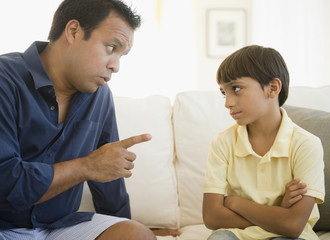 Hispanic father lecturing son