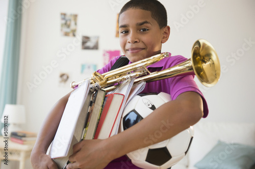Hispanic boy carrying trumpet, books and soccer ball