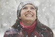 Caucasian woman looking up at snow falling