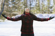 Caucasian woman standing in snow with arms outstretched