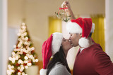 Couple in Santa hats kissing underneath mistletoe