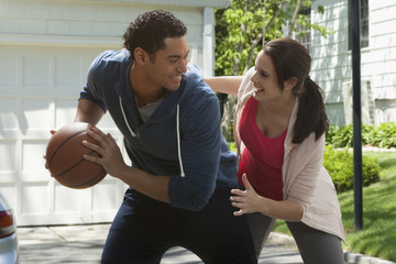Couple playing basketball in driveway