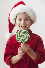 Smiling Caucasian boy in Santa hat holding lollipop