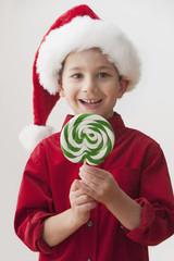Smiling Caucasian boy in Santa hat holding lollipop