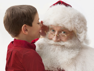 Caucasian boy telling Santa what he wants for Christmas