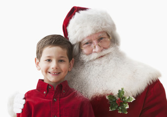 Caucasian boy standing with Santa