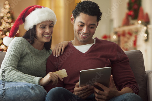 Couple using digital tablet to buy Christmas gifts