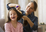Caucasian mother brushing daughter's hair