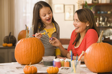 Caucasian mother and daughter decorating pumpkins
