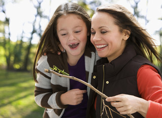 Caucasian mother and daughter looking at praying mantis