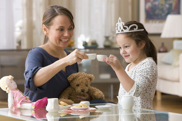 Caucasian mother and daughter having tea party