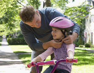 Caucasian father helping daughter with bicycle helmet