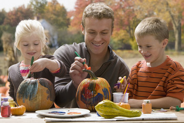 Caucasian father and children decorating pumpkins