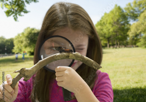 Caucasian girl looking through magnifying glass at caterpillar