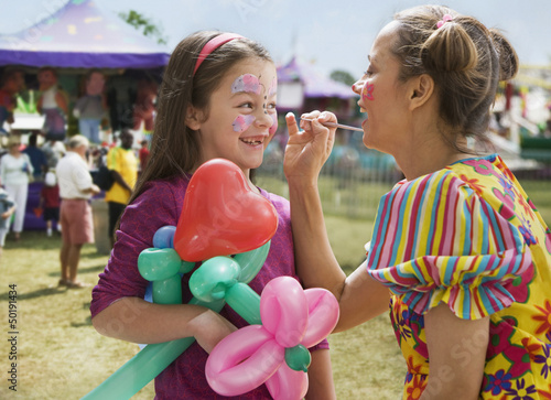 Caucasian girl having face painted at fair
