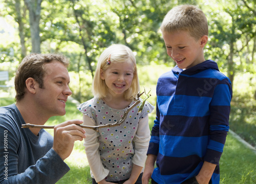 Caucasian father and children looking at praying mantis