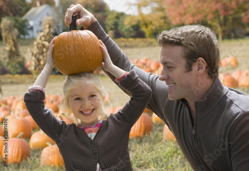 Caucasian father watching daughter with pumpkin on her head