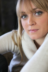 Blond woman in winter jumper sat on sofa