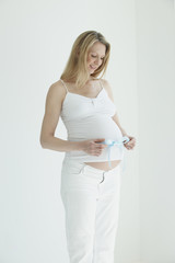 Caucasian woman trying ribbon around pregnant stomach