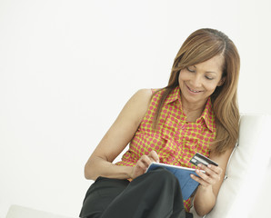 African American woman shopping on digital tablet with credit card