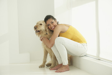 Hispanic woman hugging dog