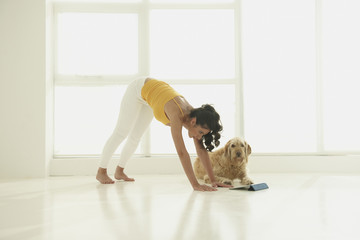 Hispanic woman stretching on floor with dog and digital tablet