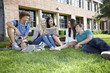 School friends hanging out on grass with digital tablet