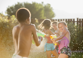 Children squirting each other with water guns