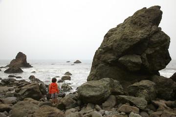 Mixed race climbing on rocks near ocean