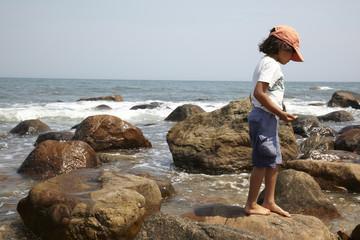 Mixed race boy standing on rocks near ocean