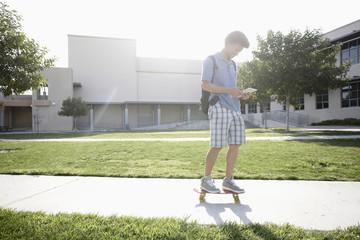 Mixed race boy on skateboard