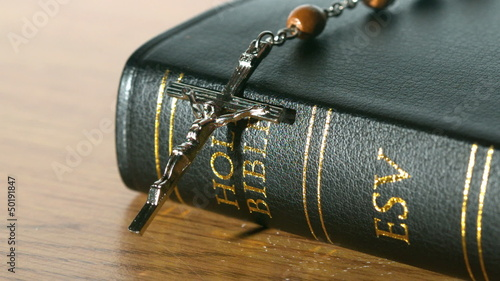 Rosary beads falling onto bible on a table